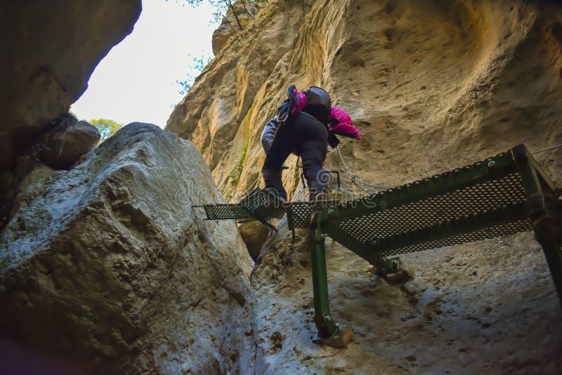 接近有背包的徒步旅行者攀登一个石墙跨步在一些绿色步的攀登山的垂直的空白得到 库存图片