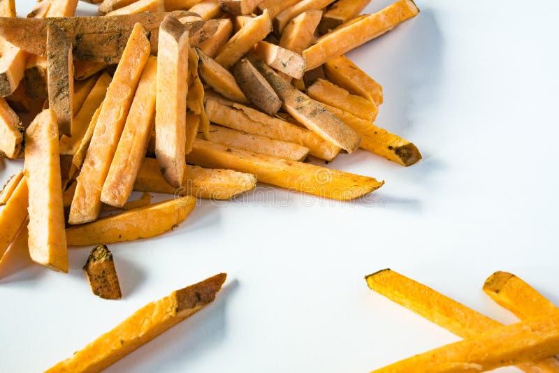 接近的反对白色背景的堆未加工的地瓜土豆片 库存照片