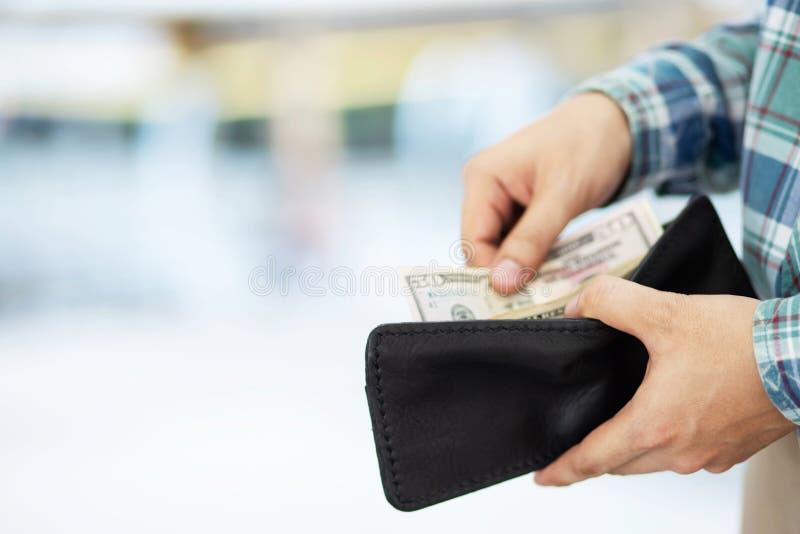 接近的商人格子衬衫在一个人的手上的拿着一个钱包采取金钱在口袋外面 费用财务概念 Leav 库存图片