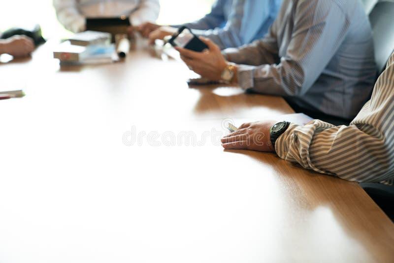 接近的商人的手,他们在木桌上一起谈话在下午 免版税库存图片