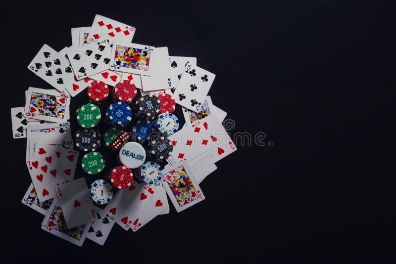 接近的堆不同的色的纸牌筹码,纸牌和切成小方块隔绝在与拷贝的黑赌博娱乐场桌背景 免版税库存图片