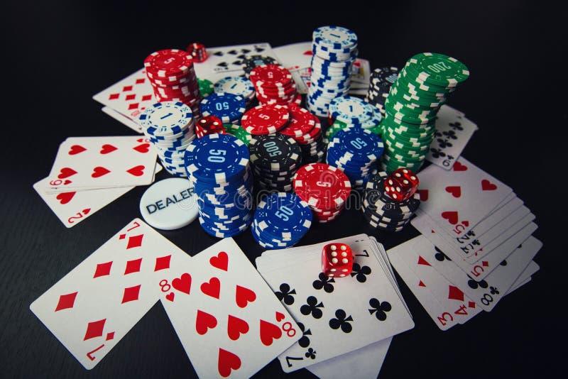 接近的堆不同的色的纸牌筹码,纸牌和切成小方块隔绝在黑赌博娱乐场桌背景 ?? 库存图片