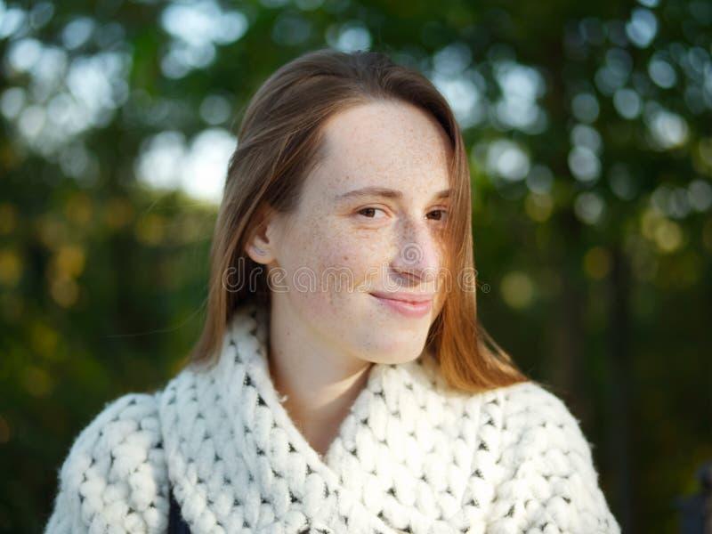 接近的射击年轻时髦穿戴的严肃白种人妇女摆在室外在都市城市公园被弄脏的背景冷天 图库摄影