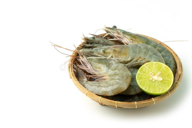 接近的小组新鲜的未加工的和平的白色虾和柠檬在竹碗在白色背景孤立背景 库存图片