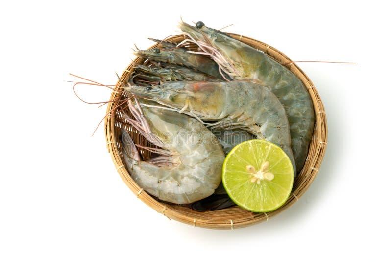 接近的小组新鲜的未加工的和平的白色虾和柠檬在竹碗在白色背景孤立背景 免版税库存图片