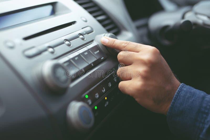 接近的手开放汽车收音机听 他的车多媒体系统的汽车司机改变的转动的按钮电台 ?? 免版税库存照片