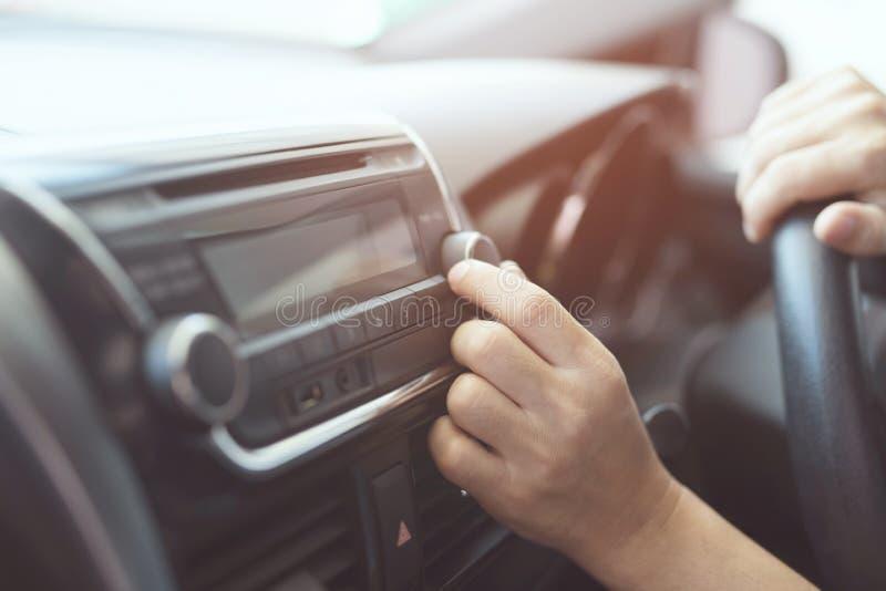 接近的手开放汽车收音机听 汽车司机改变的转动的按钮电台 图库摄影