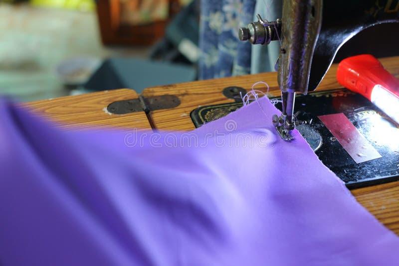 接近的手,亚裔妇女捉住美好的织品,紫色,缝合,切开妇女礼服,缝合与老机器,葡萄酒 库存图片