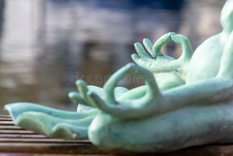 接近的手 做瑜伽的石青蛙室外 禅宗放松和放松瑜伽在自然背景 免版税库存照片