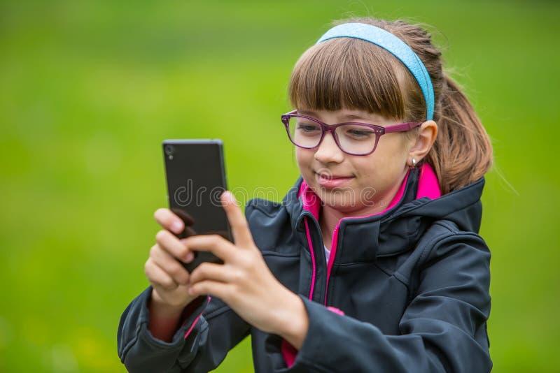接近的有手机的画象小女孩 有站立和发短信的小女孩与电话 免版税库存照片