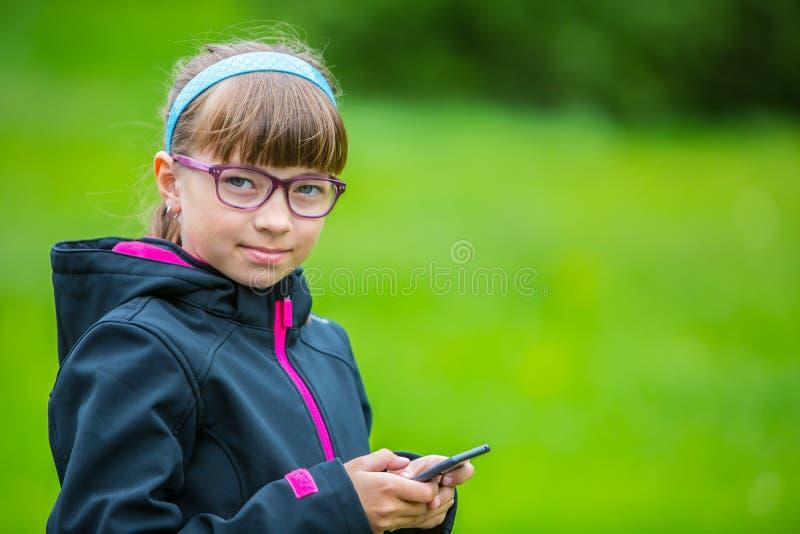 接近的有手机的画象小女孩 有站立和发短信的小女孩与电话 免版税库存图片