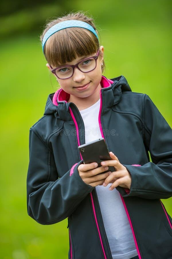 接近的有手机的画象小女孩 有站立和发短信的小女孩与电话 库存照片