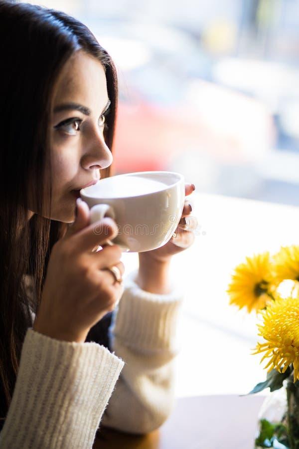 接近的画象年轻美丽的愉快的妇女饮用的咖啡和看通过窗口 库存照片