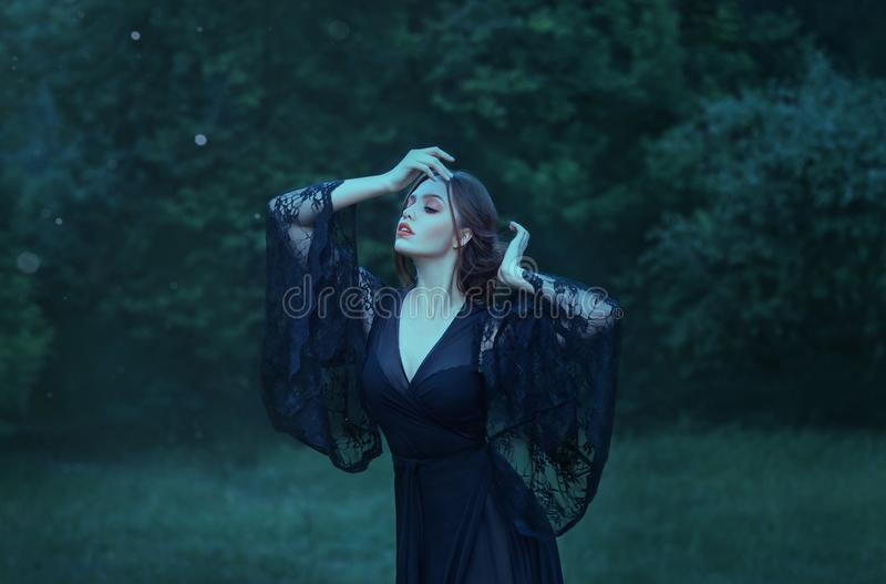 接近的眼睛,在月光的女孩跳舞在单独黑暗的鲜绿色森林里 魔术 巫婆 守护程序 佩带长的黑色 免版税库存图片
