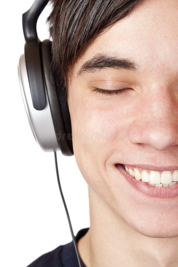 接近的耳机听音乐少年  图库摄影