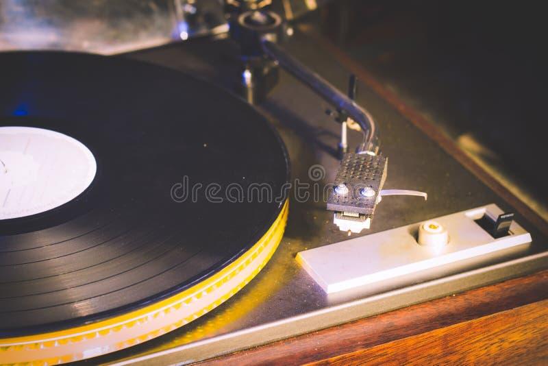 接近的葡萄酒的留声机老使用的歌曲 演奏老歌曲,有乙烯基圆盘的葡萄酒电唱机 库存图片
