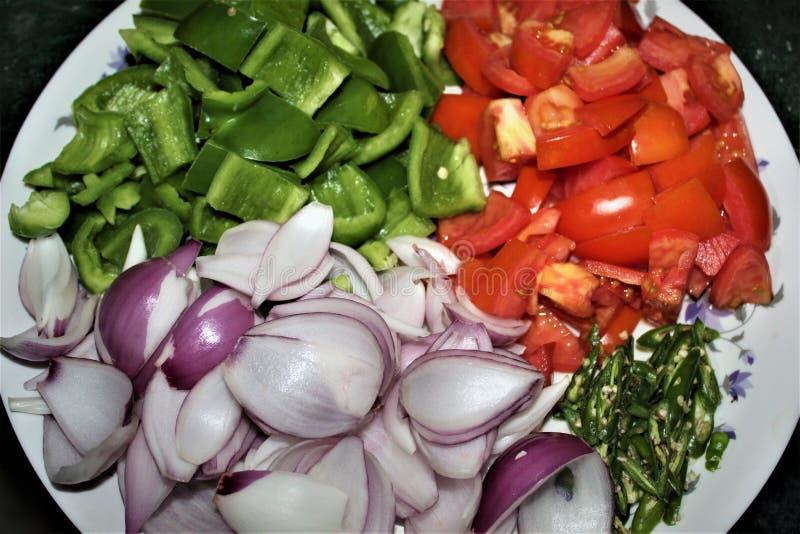 接近的观点的象蕃茄、辣椒的果实、葱和辣椒的切好的菜 免版税库存图片