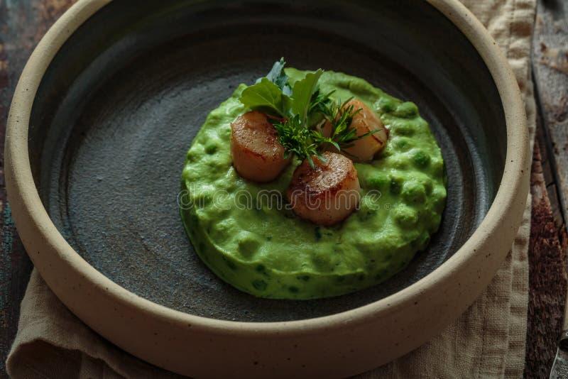 接近的观点的Seared扇贝用在板材的豌豆纯汁浓汤 免版税库存照片