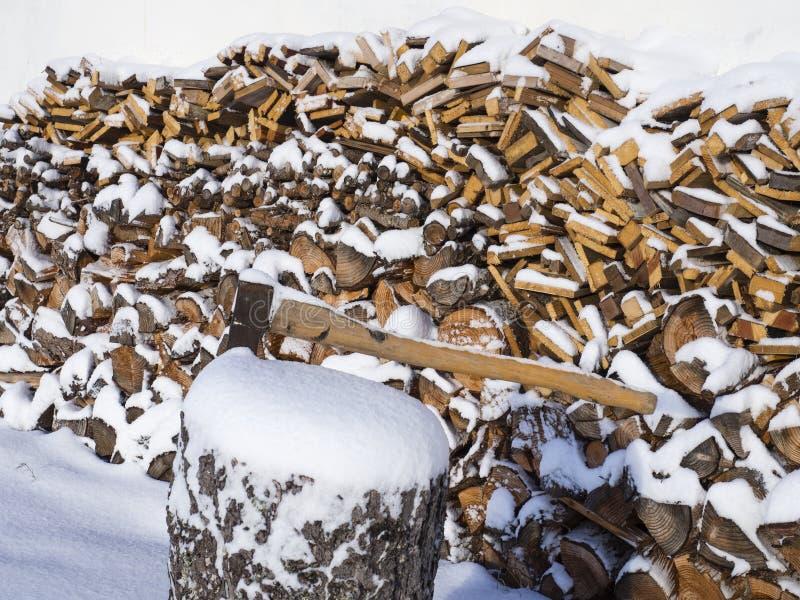 接近的轴附有树的树干在用雪盖的被堆的切好的木柴背景的  免版税图库摄影