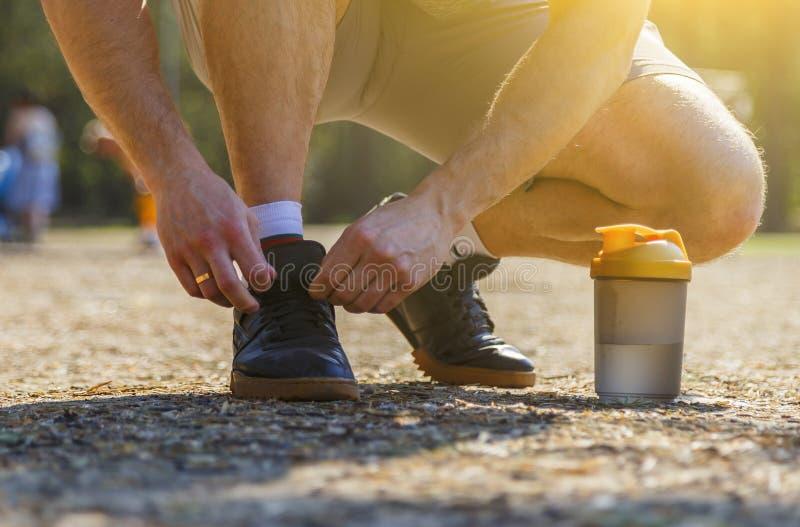 接近的运动员系带他的黑运动鞋在森林公路的阳光下 ?? 健康活动 ?? 免版税库存照片