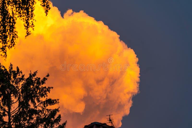 接近的雷暴的桔黄色云彩在明媚的阳光下 库存图片