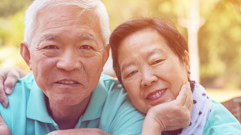 接近的面孔愉快的eldery亚洲夫妇微笑一起以绿色 库存图片