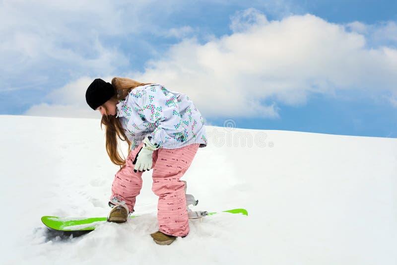 接近的fastering的女孩雪板年轻人 免版税库存照片