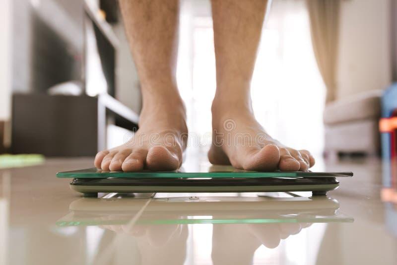 接近站立在标度称的人脚 免版税图库摄影