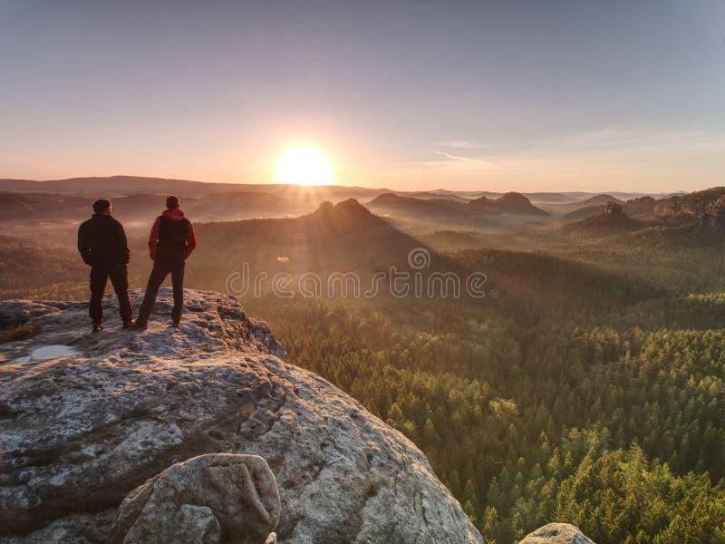 接近边缘的两个人在峭壁,观看唤醒自然 库存图片