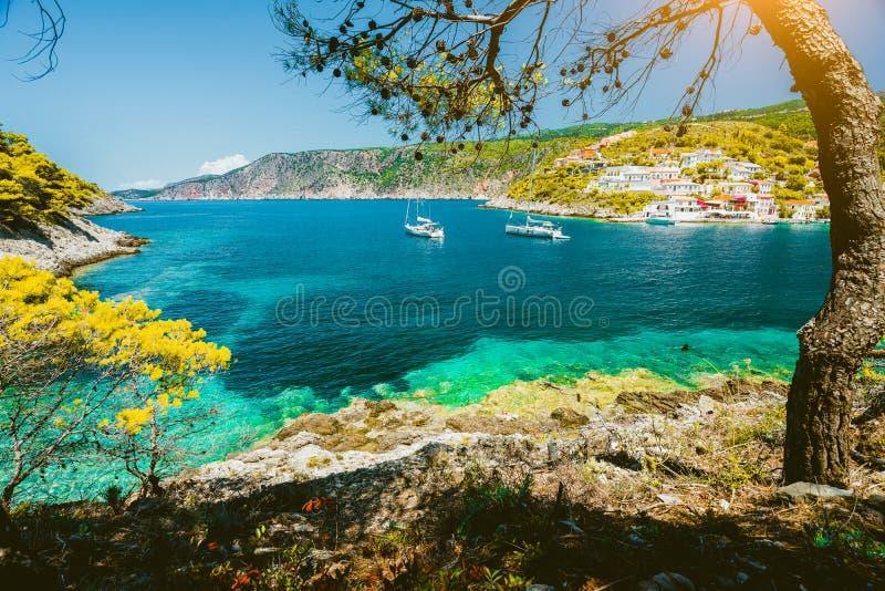 接近Assos村庄,Kefalonia的舒适绿松石海湾 希腊 白色帆船在美丽的鲜绿色色的盐水湖 免版税库存图片