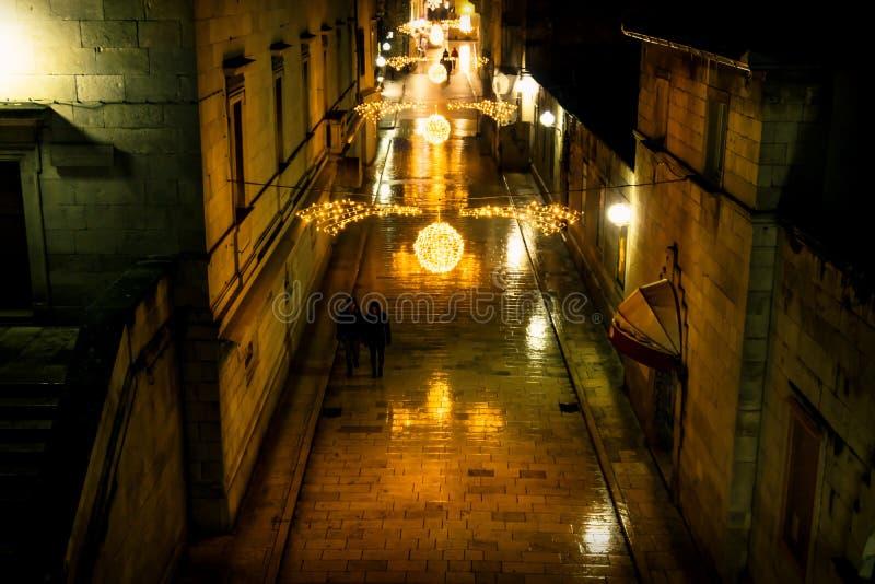 接近silhouttes走沿装饰的chrismas在晚上修补了扎达尔,克罗地亚街道  免版税库存照片