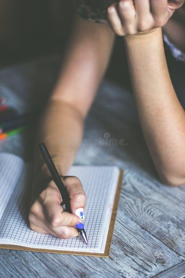 接近woman& x27;s在有各种各样的项目的木桌面安置的笔记薄的手文字 库存图片