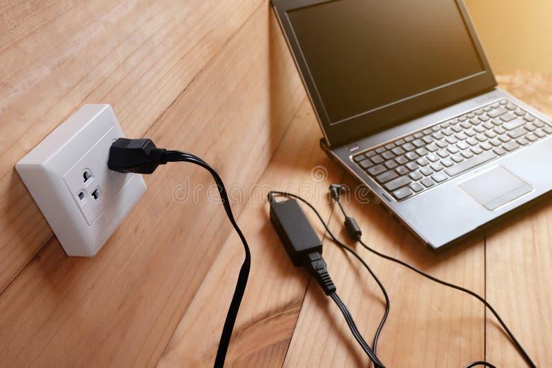 接通适配器便携式计算机电源线充电器在木的 免版税库存图片