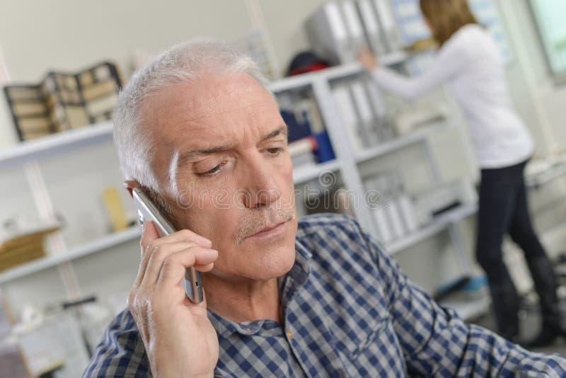 接重要电话的资深办公室工作者 免版税库存照片
