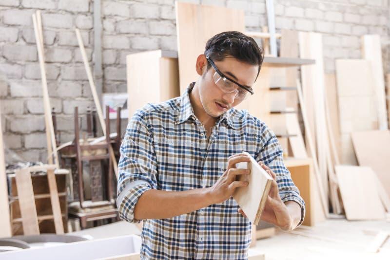 控制他的产品的年轻木匠质量 免版税库存图片