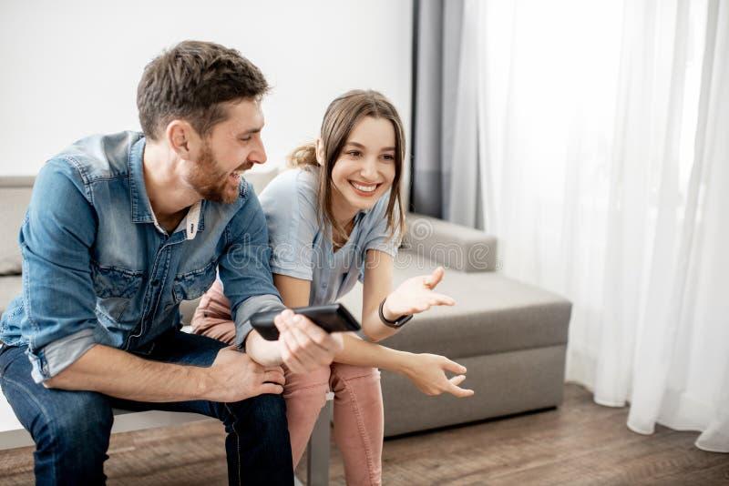 控制夫妇重点家远程有选择性的电视注意的年轻人 免版税库存照片