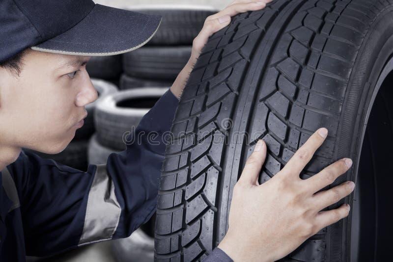 控制黑轮胎的技工 图库摄影