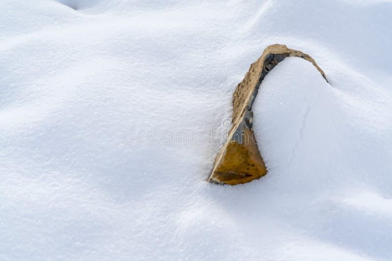推出从被日光照射了雪毯子的岩石  免版税库存照片