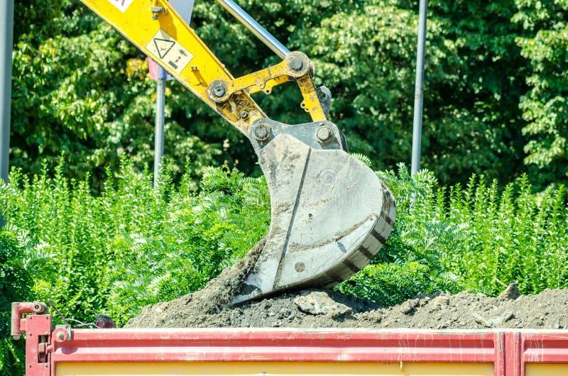 推土机挖掘机装货研了到在街道重建站点的倾销者卡车 免版税库存照片