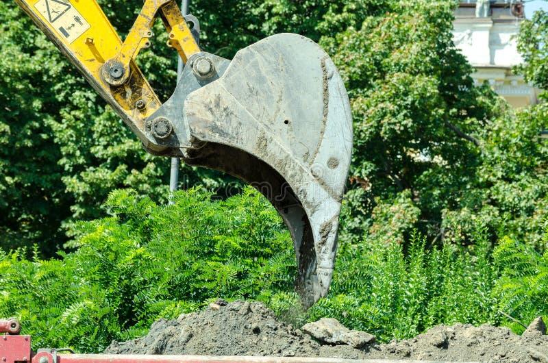 推土机挖掘机装货研了到在建造场所的倾销者卡车 免版税库存照片