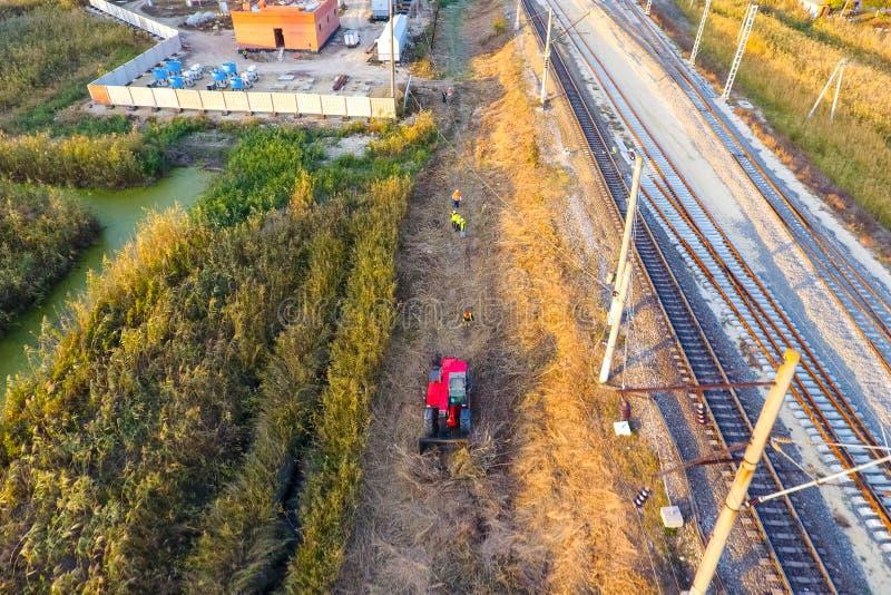 推土机清除沿铁路轨道的空间 倾斜芦苇  图库摄影