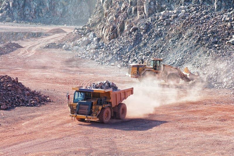 推土机装货有斑岩岩石材料的倾销者卡车在a 免版税库存图片