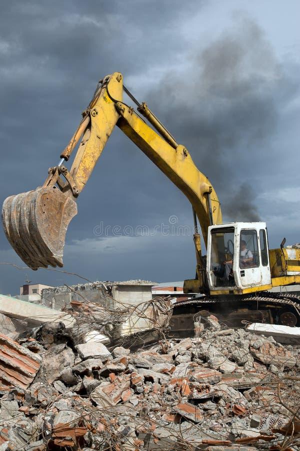 推土机从遗弃大厦的爆破取消残骸 图库摄影