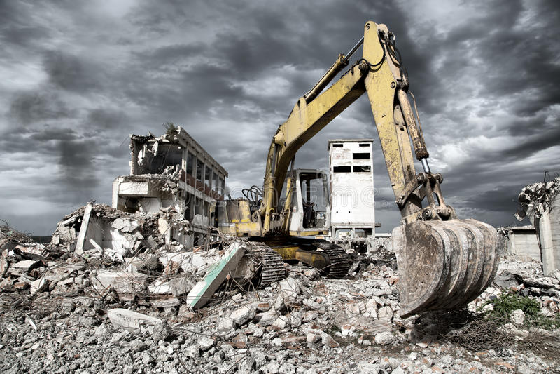 推土机从遗弃大厦的爆破取消残骸 库存图片
