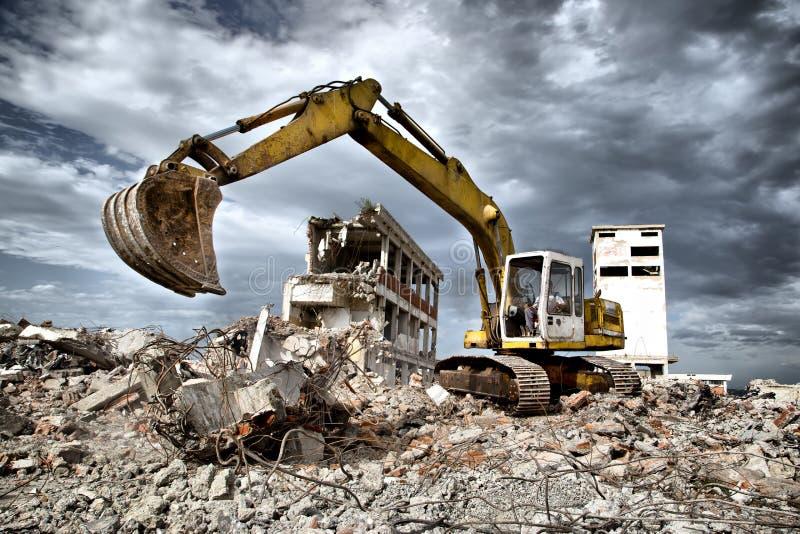 推土机从遗弃大厦的爆破取消残骸. 锤子, 挖掘机.