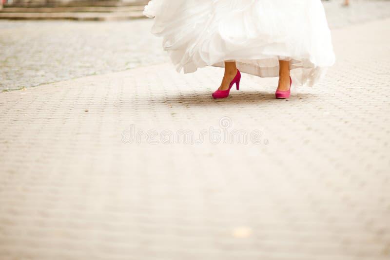 推她的紫色婚姻的鞋子-街道片刻的新娘 免版税库存照片