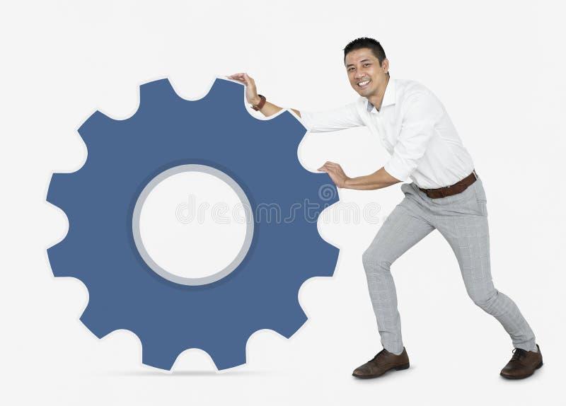 推挤一个蓝色钝齿轮的商人 图库摄影