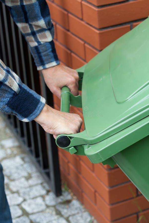推挤一个被转动的大型垃圾桶的男性手 免版税库存图片