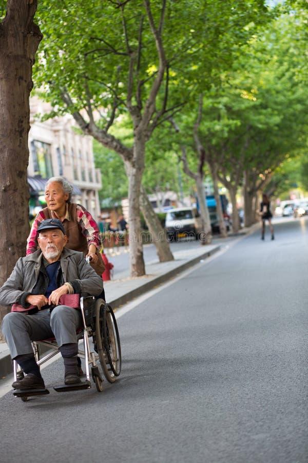 推挤一个轮椅的妇女一个老人在Shangh街道  免版税图库摄影