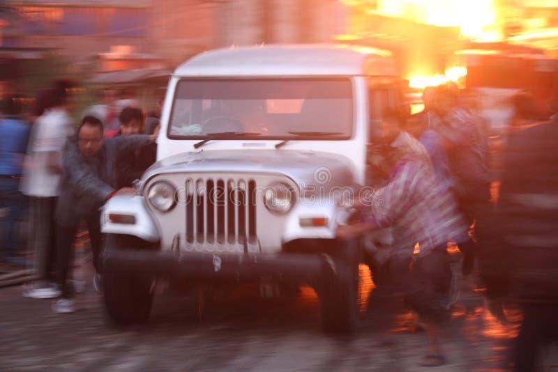 推挤一辆无人卡车/汽车远离加油站火的一个小组人 免版税库存照片